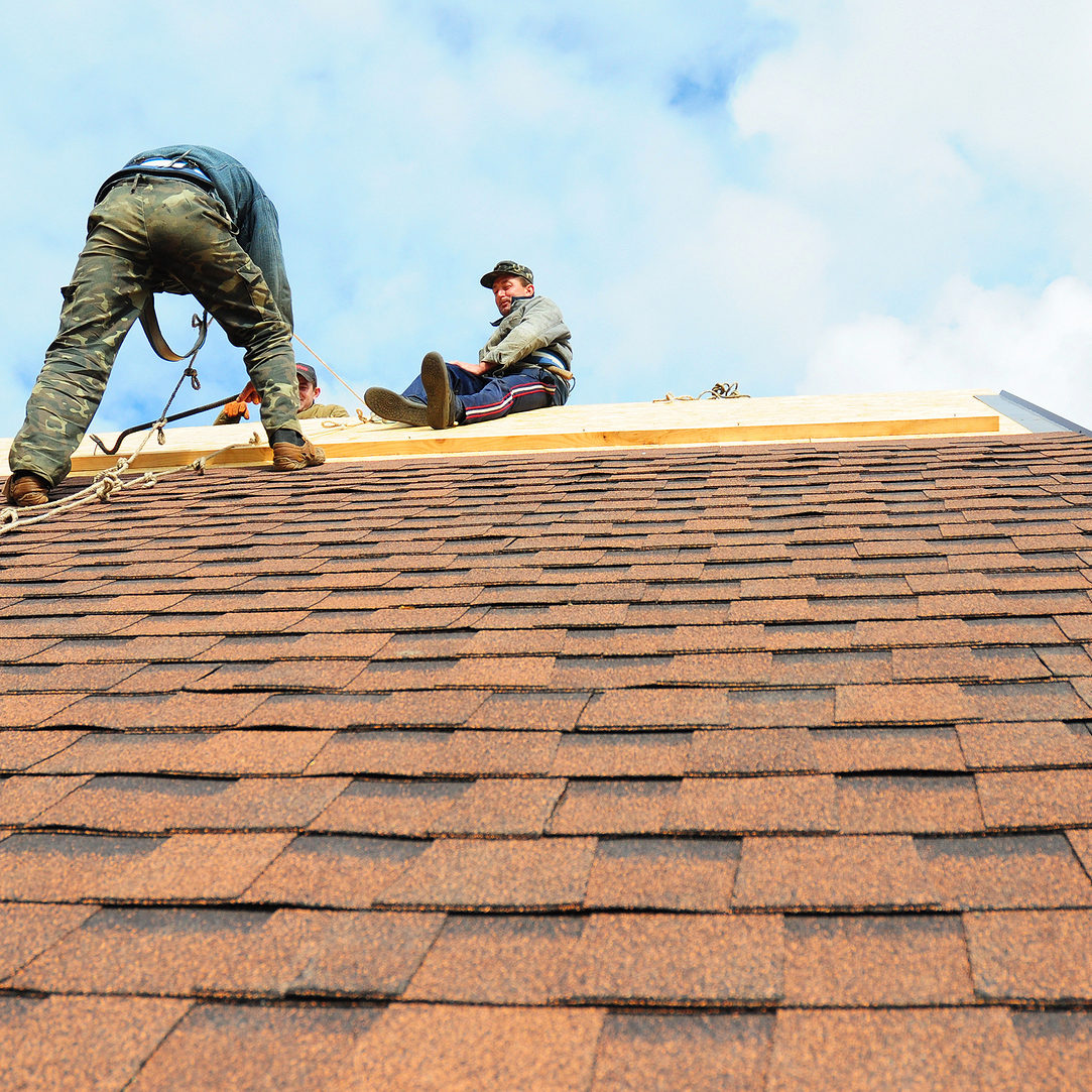 KIEV - UKRAINE JANUARY - 25 2017: Roofing Contractors Install New House Roofing with Asphalt Shingles. Roofer working on a home with safety rope. Roofing Contractor.
